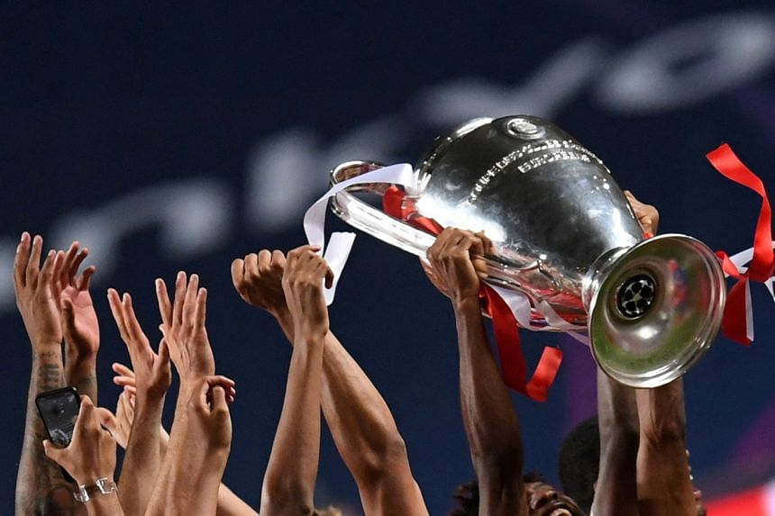 A 2020 photo shows Bayern Munich celebrating winning the Champions League with the trophy.