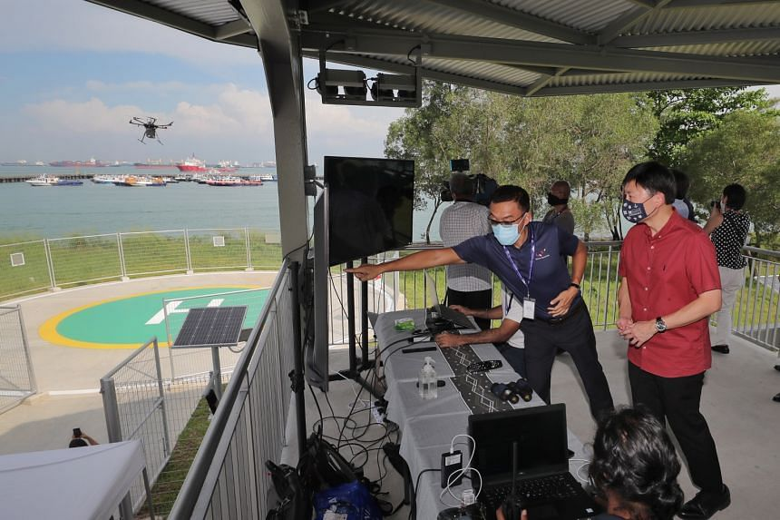 Senior Minister of State for Foreign Affairs and Transport Chee Hong Tat (right) observing a drone taking off to deliver a package on April 20, 2021.