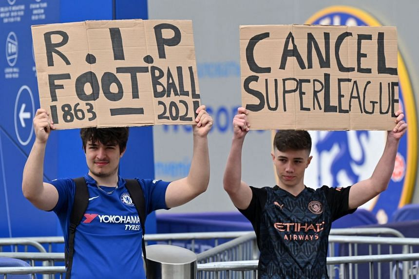 Supporters hold up placards critical of the idea of a New European Super League, outside English Premier League club Chelsea's Stamford Bridge stadium in London on April 20, 2021, ahead of their game against Brighton.
