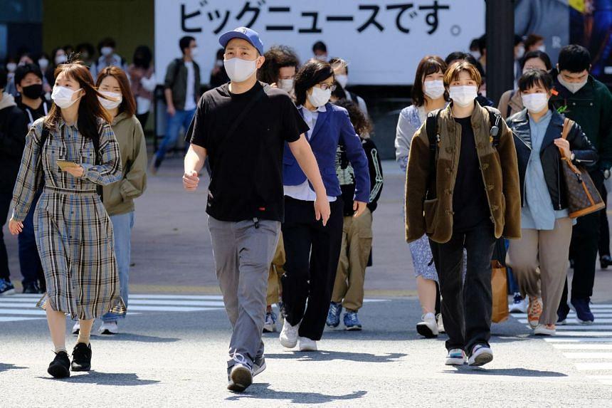 Pedestrians wearing face masks walk across Shibuya Crossing in Tokyo, on April 18, 2021.