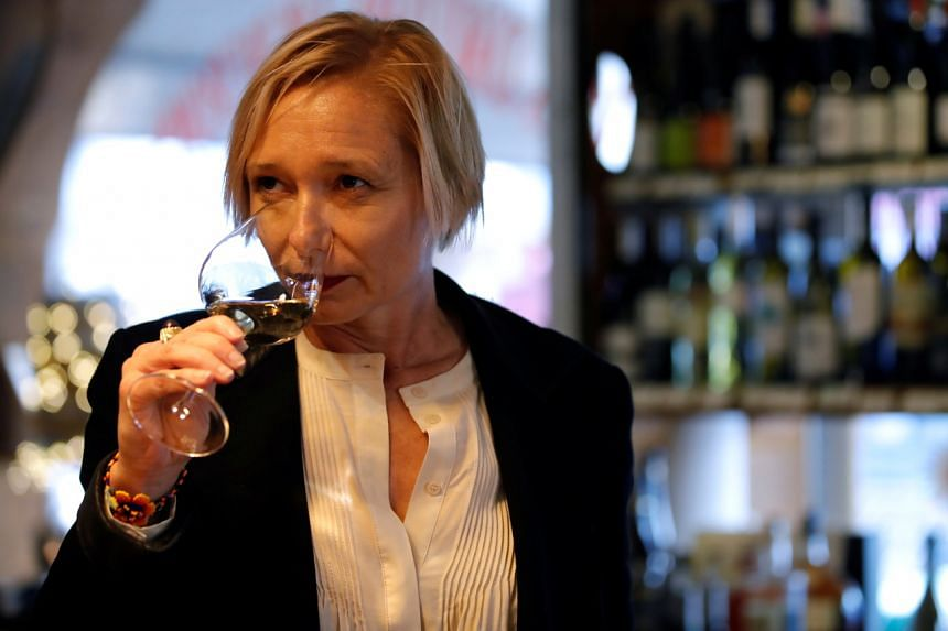 French oenologist Sophie Pallas smells wine during a wine tasting session in a shop in Paris, on April 19, 2021.