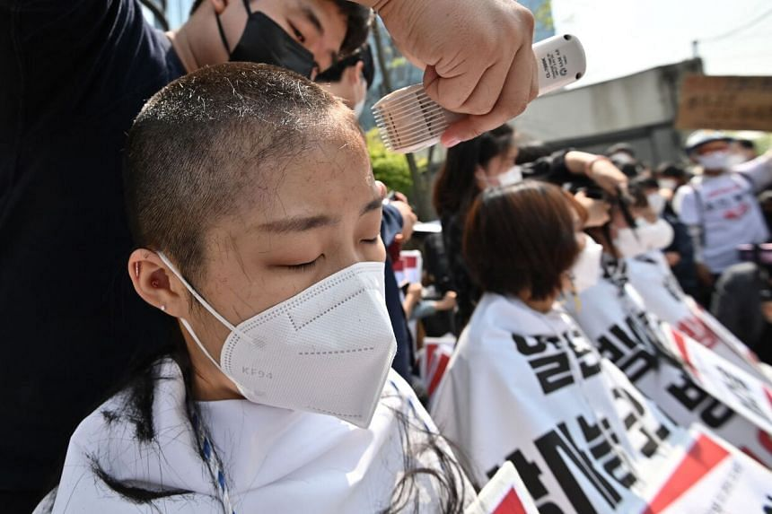 The protesters who were shaved were draped in protective sheets emblazoned with messages condemning the Japanese plan.