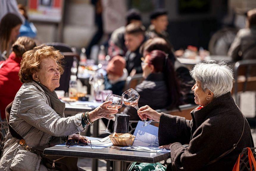 Women enjoy a glass of wine as outdoor terraces reopen in Lausanne, Switzerland, on April 19, 2021.