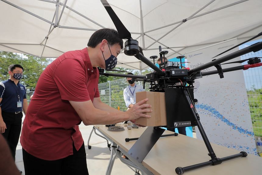 Senior Minister of State for Foreign Affairs and Transport Chee Hong Tat loading a package into a drone at Marina South on April 20, 2021.