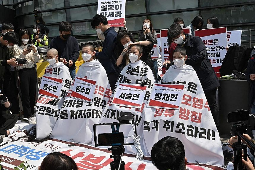 South Korean college students having their heads shaved outside the Japanese embassy in Seoul yesterday in protest against Japan's decision to release treated water from its crippled Fukushima nuclear plant into the sea. Japan last week said it will
