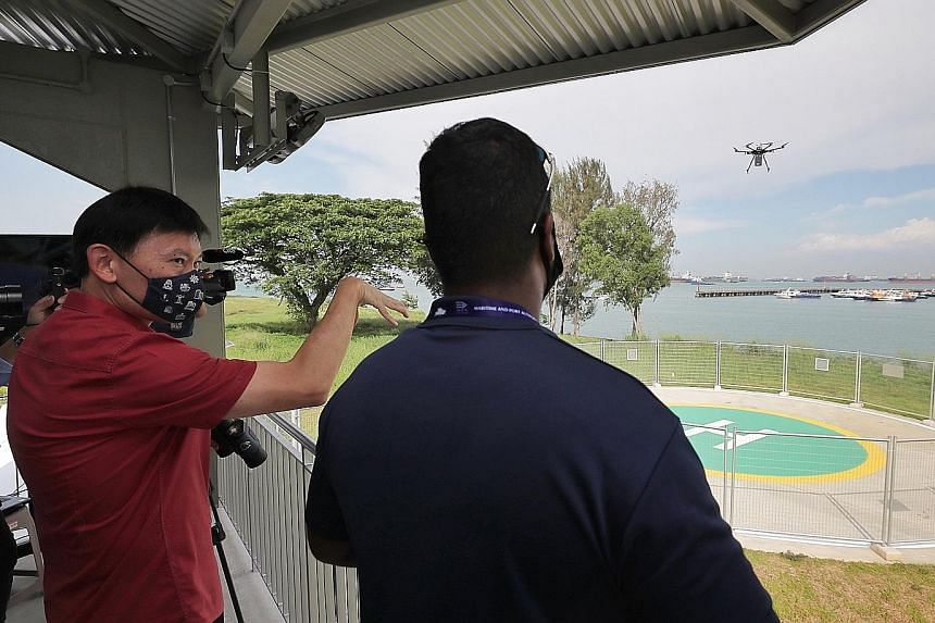 Senior Minister of State for Foreign Affairs and Transport Chee Hong Tat at the Maritime Drone Estate near Marina South Pier yesterday as a drone took off to deliver a package to a ship anchored offshore. The new space will enable maritime drone flie