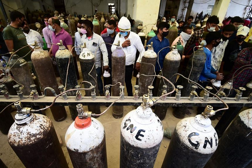 People refill medical oxygen cylinders for Covid-19 patients at an oxygen refill station in Allahabad, India, on April 20, 2021.