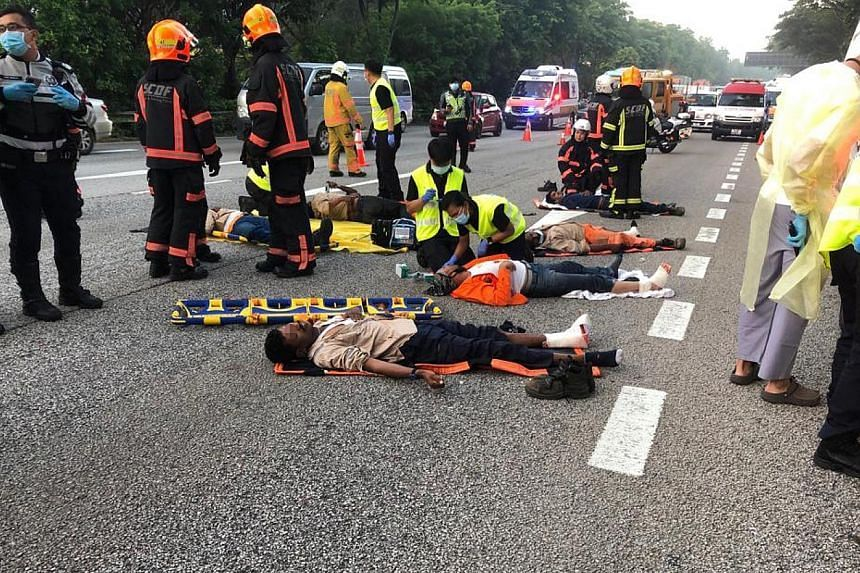 SCDF officers attending to migrant workers who were in the back of a lorry when the vehicle hit a stationary tipper truck on the PIE on April 20, 2021.
