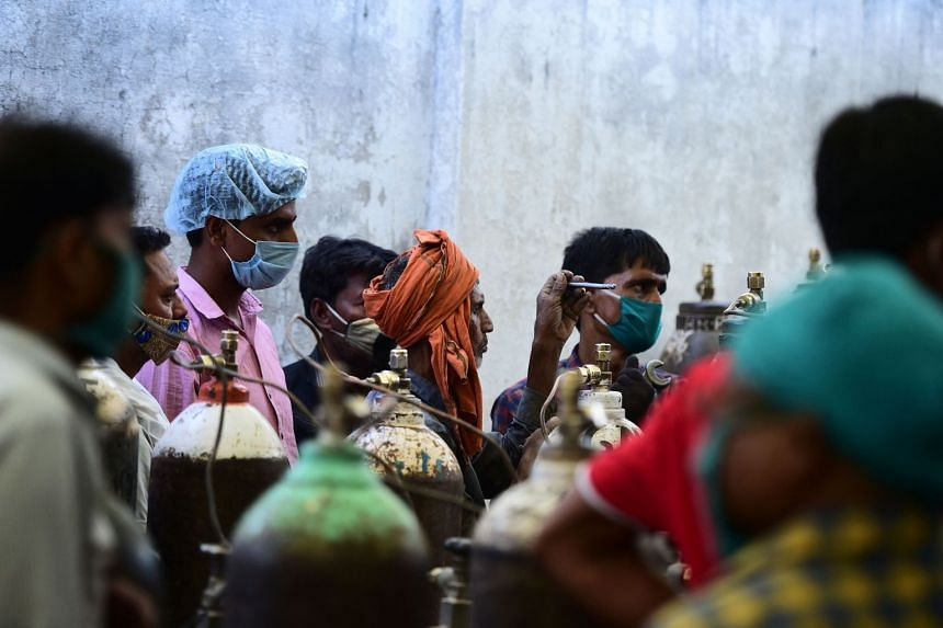 People refill medical oxygen cylinders for Covid-19 coronavirus patients at an oxygen refill station in Allahabad on April 20, 2021.