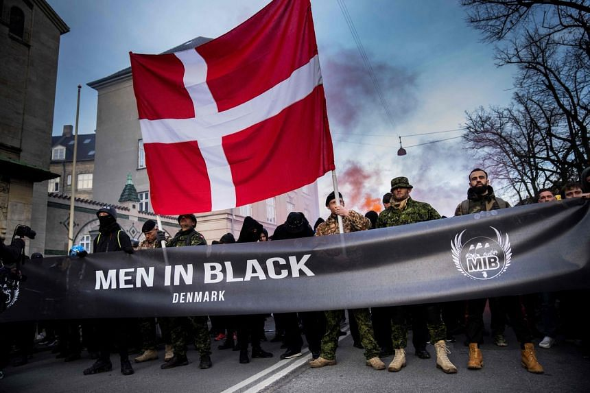 "Demonstrators taking part in a march organised by the ""Men In Black"" in Copenhagen on April 10, 2021."