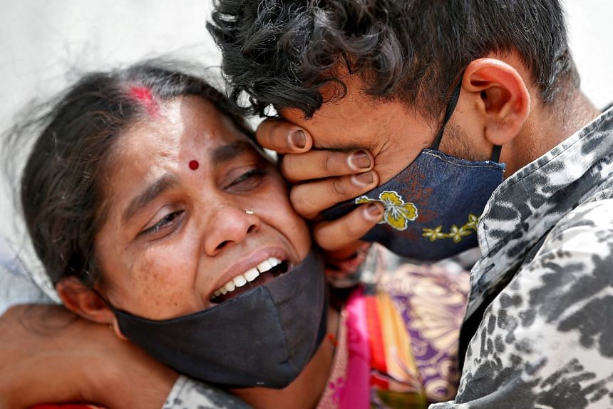 A woman mourns with her son after her husband died from Covid-19, outside a mortuary in Ahmedabad, India.