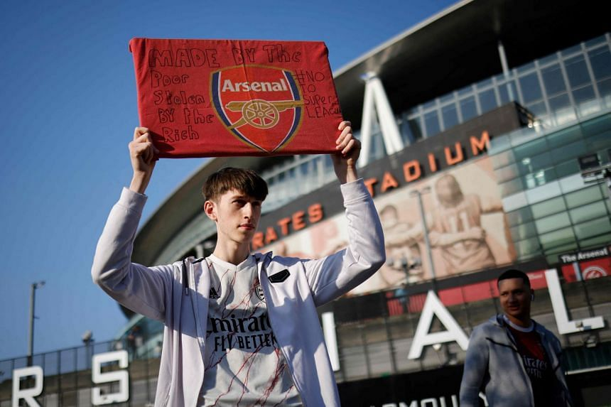 An Arsenal fan stands with an anti-European Super League banner outside the Emirates Stadium.