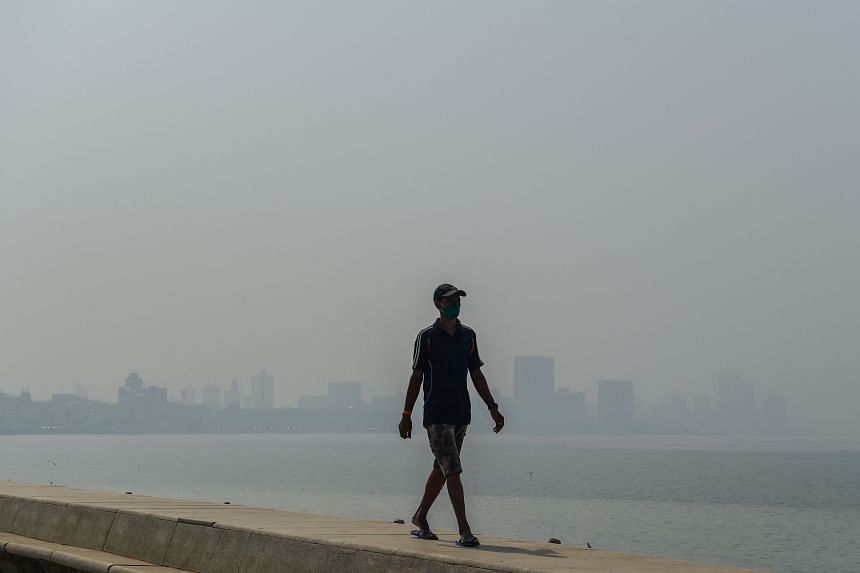 >A man walks at the sea front during a hazy day in Mumbai on February 23, 2021.