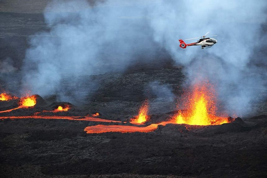 A helicopter flying over Piton de la Fournaise volcano as lava erupts on April 10, 2021, on the French Indian Ocean island of Reunion.