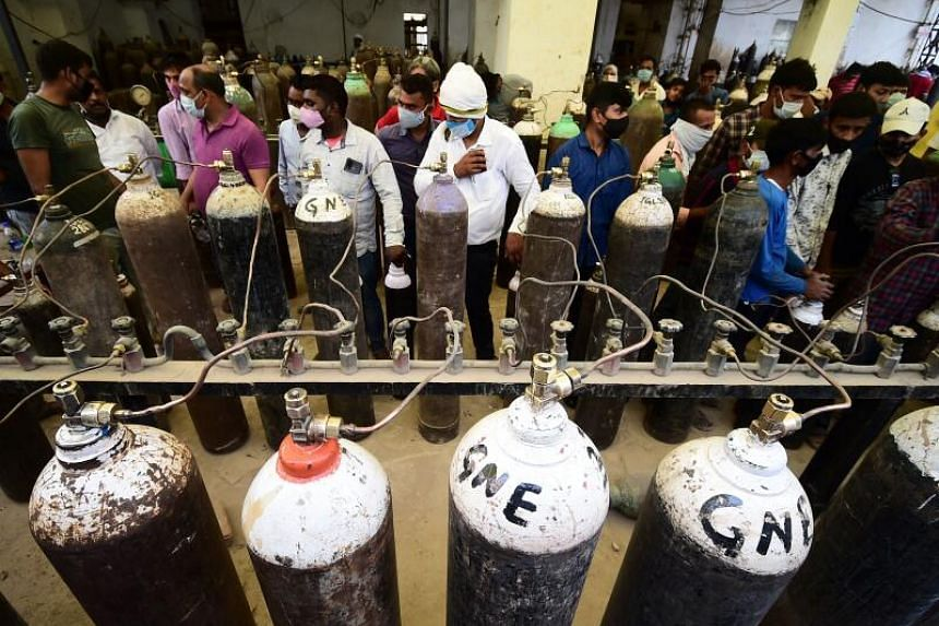 People refilling medical oxygen cylinders for Covid-19 patients at a refill station in Allahabad on April 20, 2021.