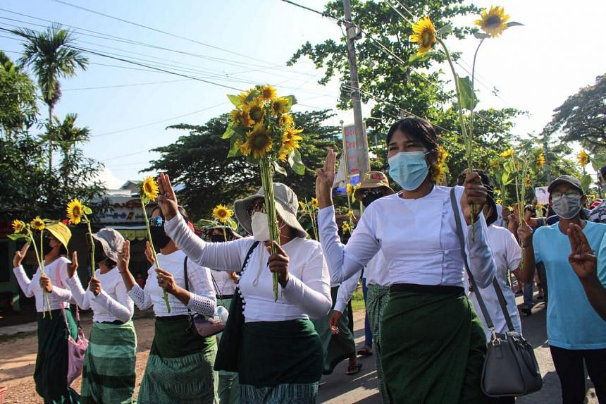 Protesters hold sunflowers during a demonstration against the military coup in Dawei, Myanmar, on April 21, 2021.