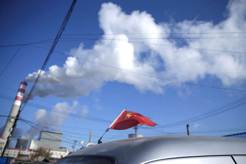 A 2019 photo shows a Chinese flag on top of a car near a coal-fired power plant in Harbin, Heilongjiang province, China.