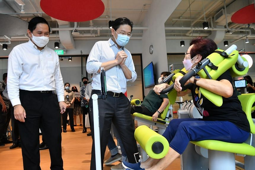 Education Minister Lawrence Wong speaks with a resident as she exercises at the Gym Tonic in SPACE @ Woods Square on April 23, 2021.