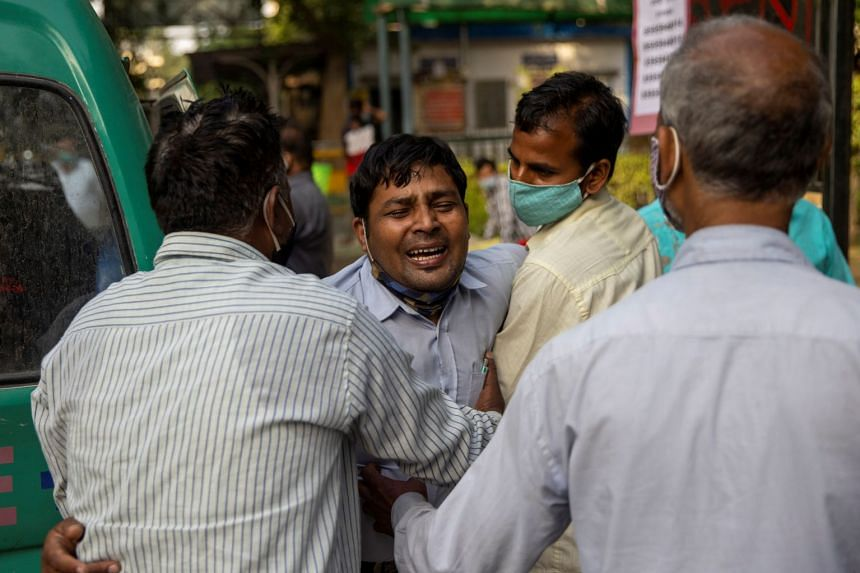 Family members mourn after a man is declared dead outside the Covid-19 casualty ward, at Guru Teg Bahadur hospital in New Delhi, on April 23, 2021.