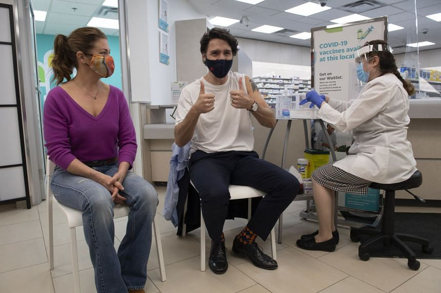 Justin Trudeau gives a thumbs up before receiving a dose of the AstraZeneca Covid-19 vaccine with his wife Sophie Gregoire Trudeau.