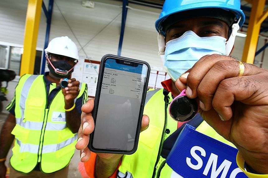 A safe management officer at a construction site showing a proximity device, which can detect workers' distance from one another. Technology has helped to make compliance with safety measures easier for many workers. PHOTO: LIANHE ZAOBAO