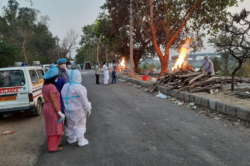 At a cremation ground in Ghaziabad, several bodies are being cremated using wooden funeral pyres.