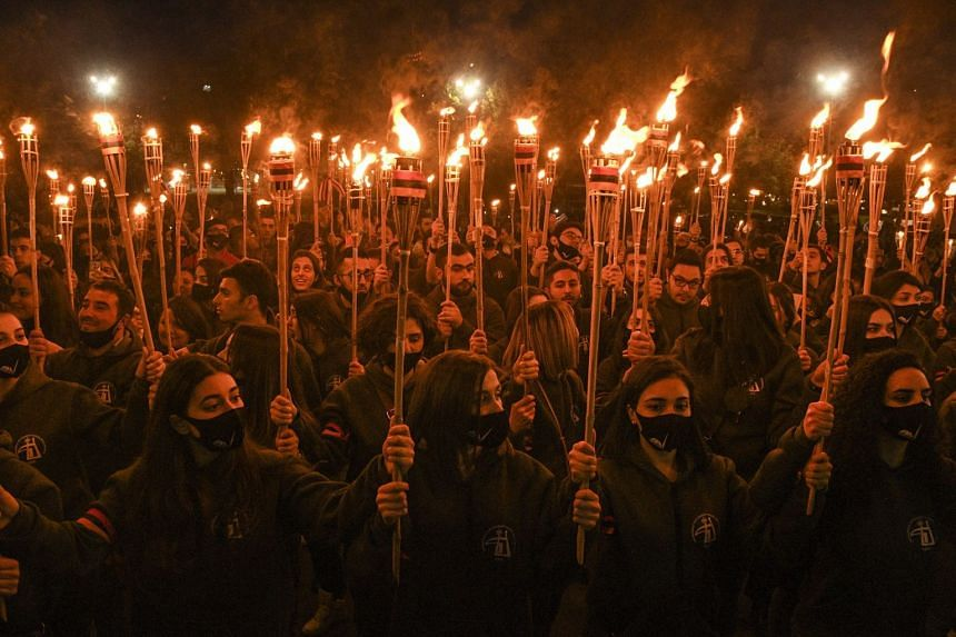 People take part in a traditional torchlight procession to mark the 106th anniversary of the mass killings of Armenians in the Ottoman Empire, in Yerevan, Armenia, on April 23, 2021.
