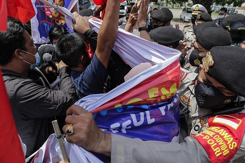 Police officers dispersing protesters during a rally against Myanmar's junta near the Asean secretariat ahead of the Asean leaders' meeting in Jakarta yesterday. PM Lee Hsien Loong said Asean can, and wishes to, play a constructive role to facilitate