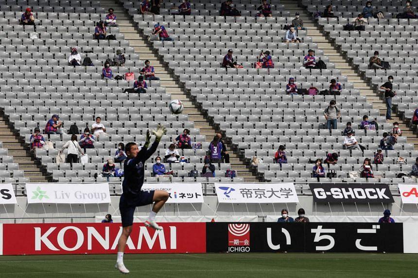 Fans sit apart to maintain social distancing at Ajinomoto Stadium in Tokyo, on April 24, 2021.