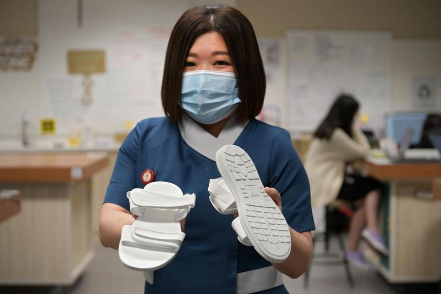 Senior Nurse Manager Loh Sok Hiang holding a pair of the Silver Generation Footwear.