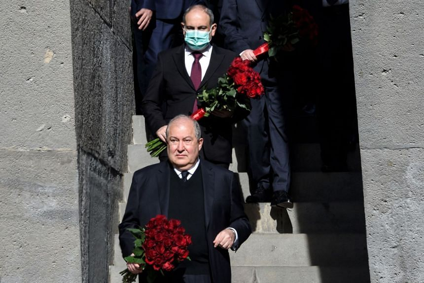 Armenia's President Armen Sarkissian (front) and Prime Minister Nikol Pashinyan lay flowers at the Tsitsernakaberd Memorial in Yerevan on April 24, 2021 to mark the 106th anniversary of World War I-era mass killings.