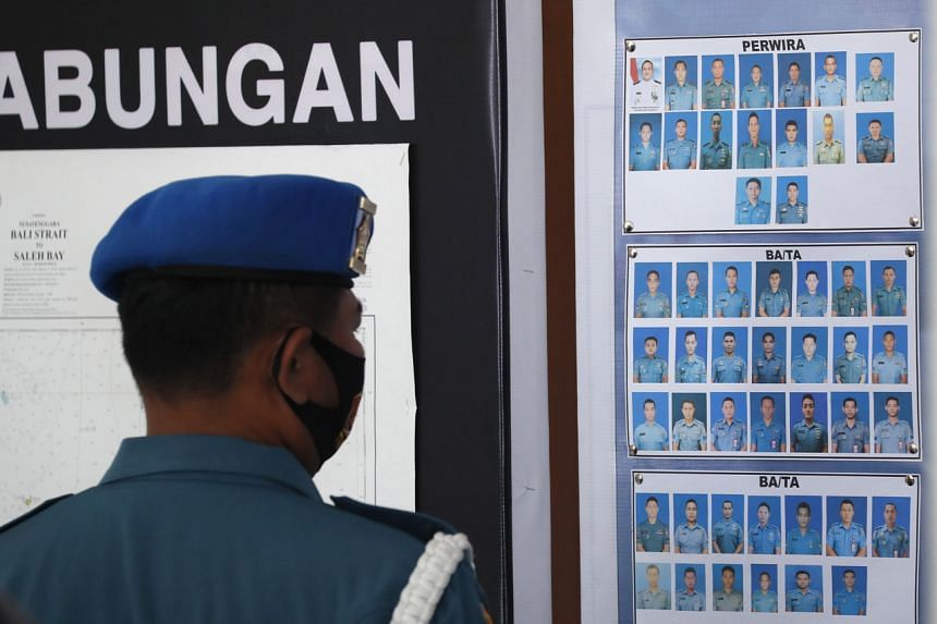 A military officer looks at pictures of crew members on the missing Indonesian Navy submarine KRI Nanggala in Bali on April 23, 2021.