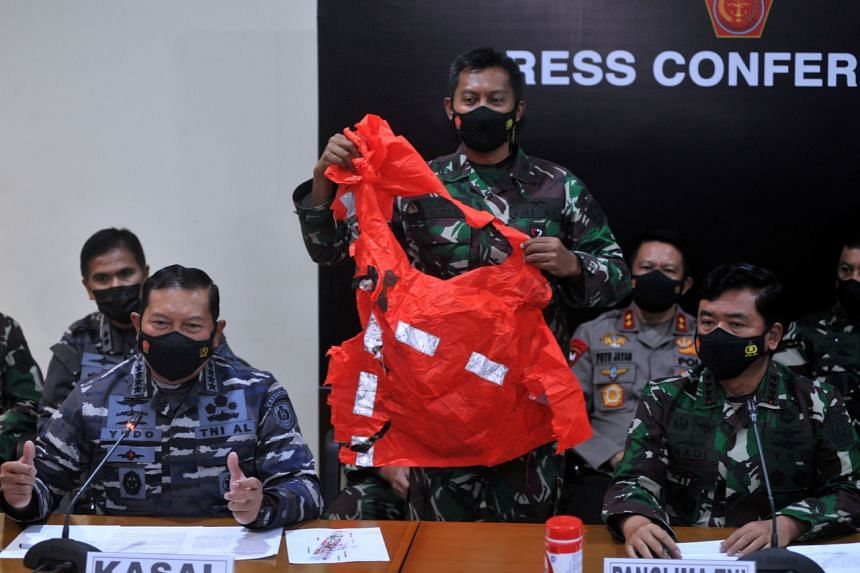 A military personnel holds an escape suit believed to be from the sunken submarine during a media conference in Bali, on April 25, 2021.