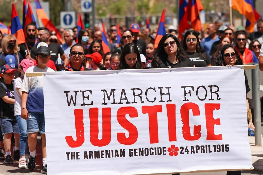 Armenians carry national flags and a large banner during a march to mark the anniversary of the 1915 Armenian genocide, in Jerusalem, on April 23, 2021.