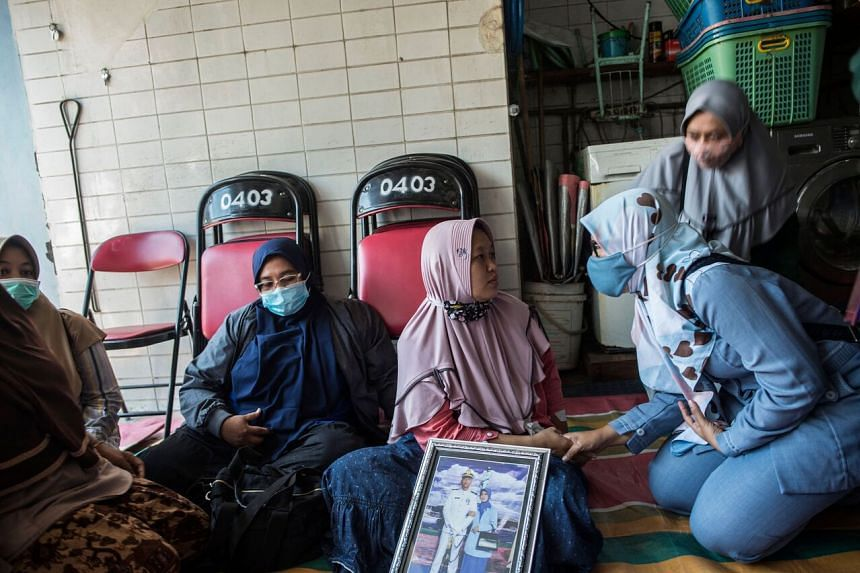 The wife of a dead crew member with his photo as she sat with family members offering prayers in Surabaya on April 26, 2021.
