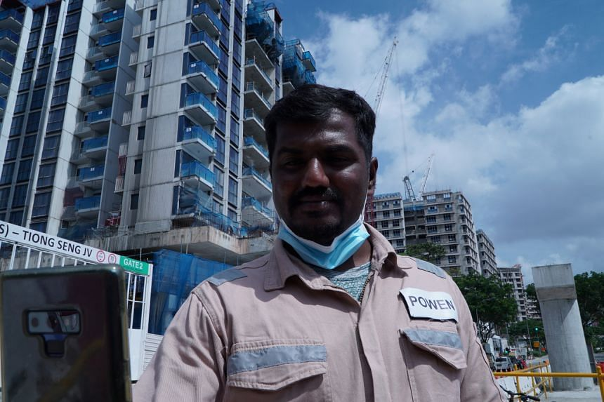 Kajima employee Gunasekar Udayakumar using the Nervotec app to scan his face through his phone's camera and check his vital signs as part of a daily check-up for employees at a construction site in Singapore.
