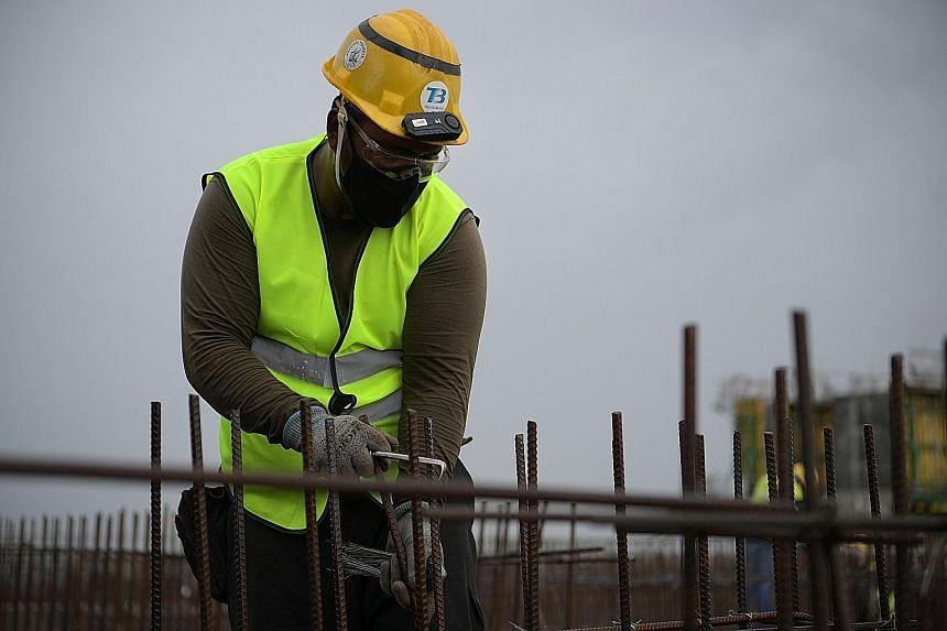 A worker with a TraceSafe contact tracing device on his safety helmet, at Boustead Singapore's construction site in Kranji in January. The Canadian firm is testing a smaller version of the device (above, right).