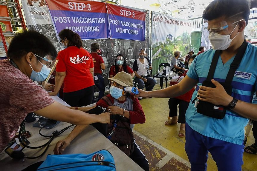 A Filipino undergoing post-vaccination monitoring after receiving a dose of the Sinovac vaccine yesterday in Quezon City, Metro Manila, where data crunchers said the number of Covid-19 cases is going down.