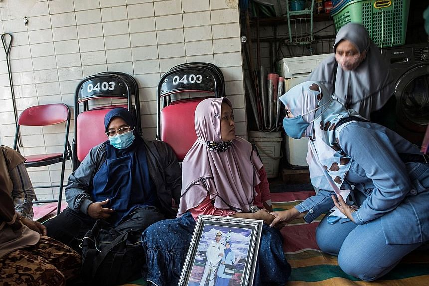 Ms Ceci Yuemi (in pink), the wife of Second Lieutenant Munawir who served on board the KRI Nanggala-402, at a religious gathering with family members in Surabaya yesterday. Family members of the lost crew will join hospital ship KRI Soeharso on Thurs