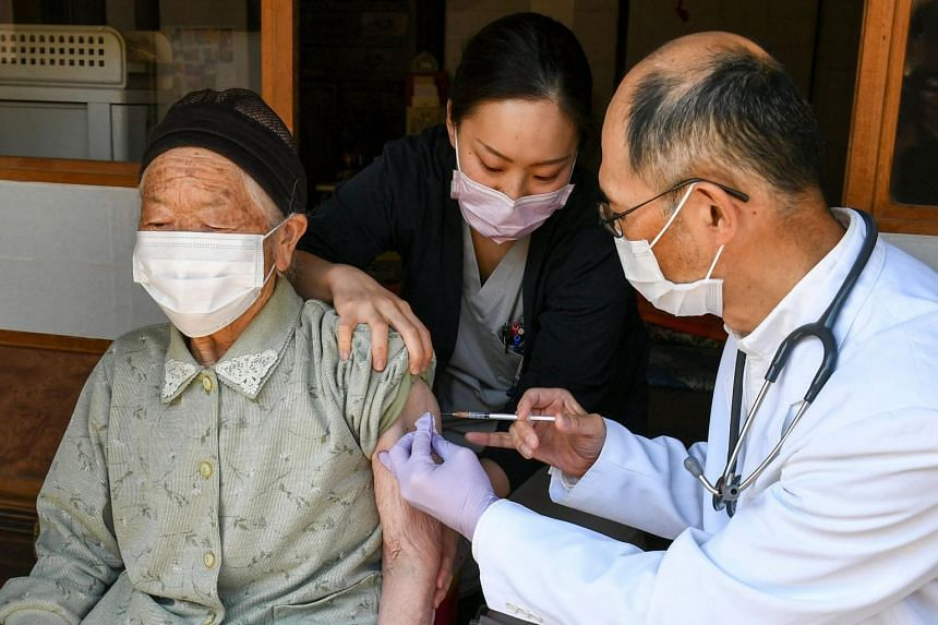 A health worker inoculates an elderly woman at Kitaaiki village in Nagano Prefecture, on April 21, 2021.