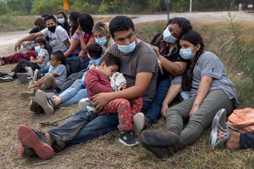 A Guatemalan family waits with fellow immigrants to board a bus to a processing centre after crossing the border from Mexico, in Texas, on April 13, 2021.