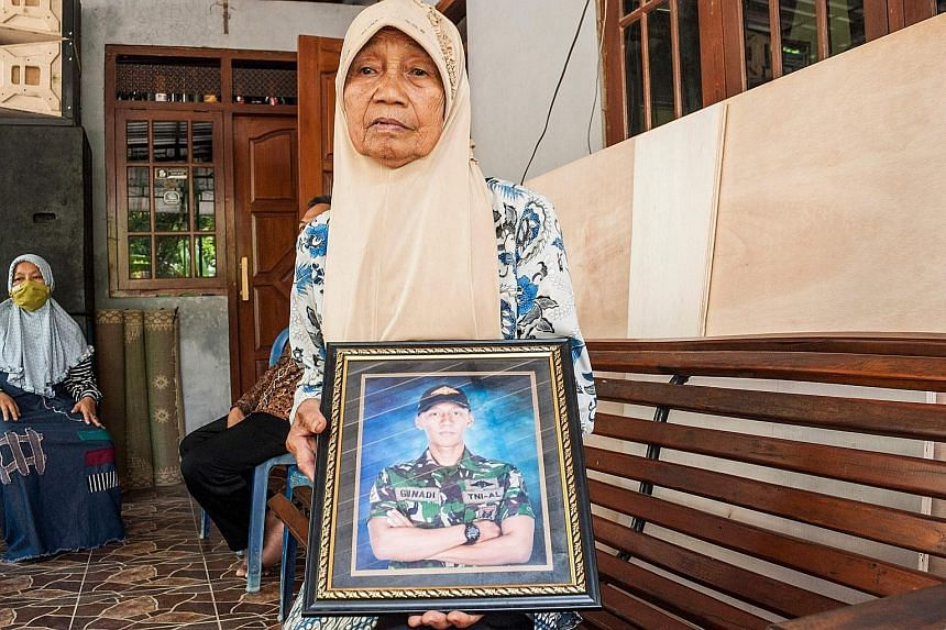 Family members of two of the submariners who died when the KRI Nanggala-402 submarine sank last Wednesday, showing photographs of their loved ones. Families of the crew have called for the Indonesian authorities to retrieve the bodies from the sea. P