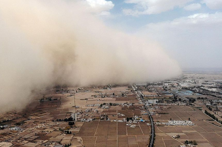 An aerial photo taken on Sunday showing a sandstorm engulfing a village in Linze county in China's north-western Gansu province. The country experiences huge dust storms each spring that lift sand from the Gobi Desert and dump it onto cities as far a
