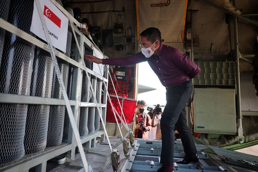 Second Minister for Foreign Affairs Maliki Osman taking a closer look at the oxygen tanks onboard a C-130 transport aircraft at Paya Lebar Air Base on April 28, 2021.