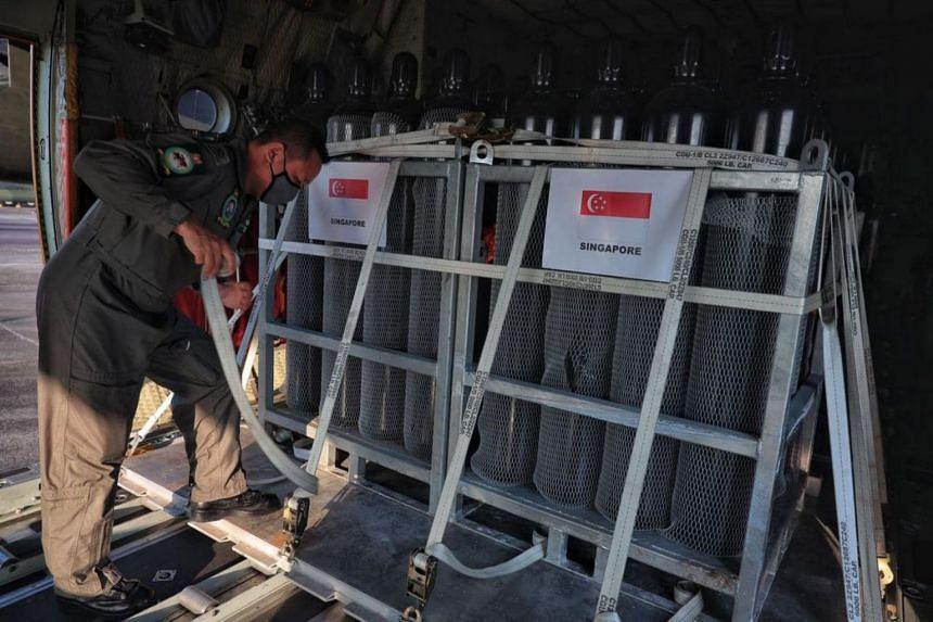 RSAF aircrew specialist Ng Kok Wee securing oxygen tanks in a C-130 transport aircraft at Paya Lebar Air Base on April 28, 2021.