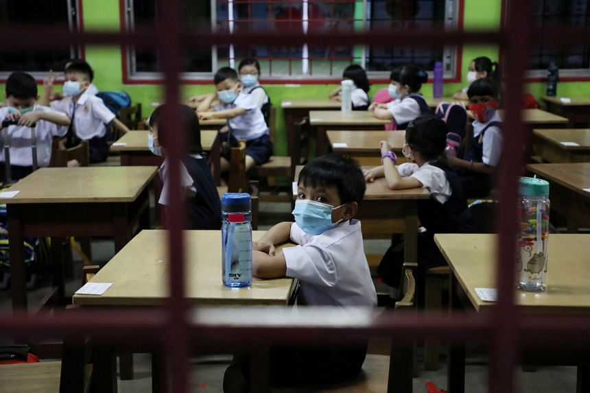 A student wearing a protective mask looks out from a classroom, as schools reopen amid the coronavirus disease outbreak, in Kuala Lumpur on March 1, 2021.