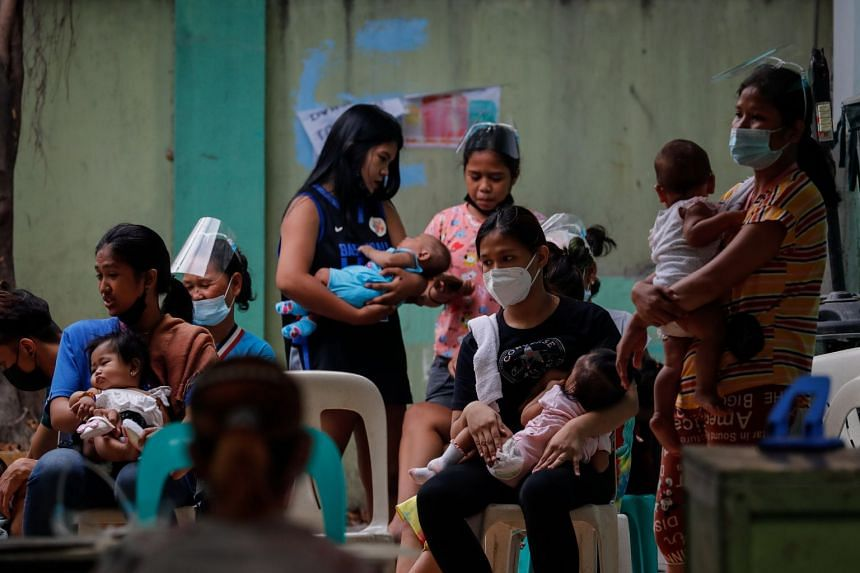 Mothers carry their babies as they line up for checkups at a public health centre in Manila, on April 27, 2021.