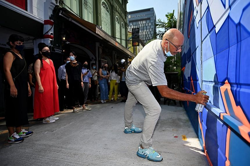 """Above: Street artist Didier """"Jaba"""" Mathieu adding the finishing touches to one of the murals along Bali Lane yesterday. Top and left: The 5m-high Graffiti Hall of Fame, a new Kampong Glam landmark, comprises stretches of street art that span nearly 2"""