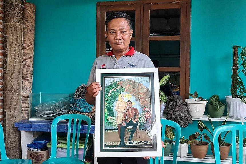 "Mr Wahyudi, an army officer whose son Pandu Yudha Kusuma died in the incident, with a photo of his son and daughter-in-law. Amid the grief, he said he was also proud of his son. ""For us military officers, to die on duty is an honour... That makes me"