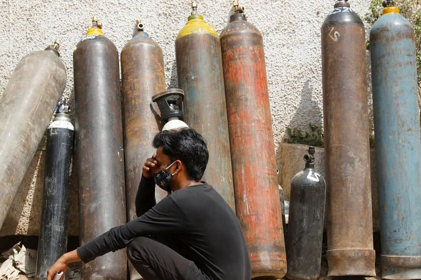 A man waits outside a factory to get his oxygen cylinder refilled in New Delhi, on April 28, 2021.
